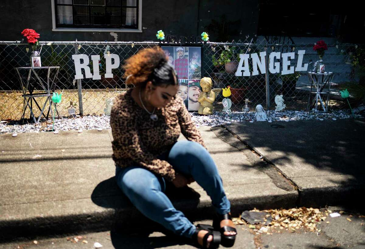 Alicia Saddler sits in front of a shrine to her brother, Angel Ramos, who was shot and killed by police. The officer said he was holding a knife.