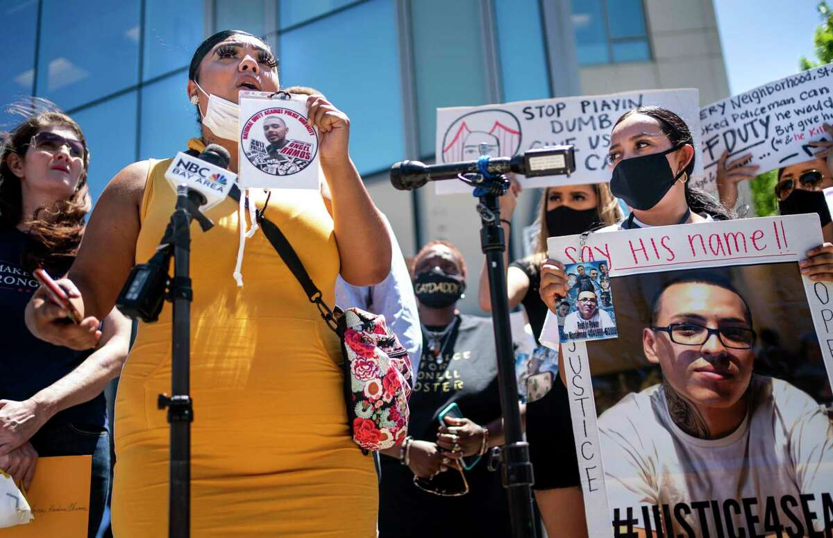 Vallejo families who have lost sons and brothers in deadly encounters with police protest Monday in front of the Solano County District Attorney's Office. Alicia Saddler holds up a photo of her dead brother, Angel Ramos.