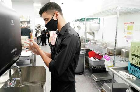 Server Gabe Rosado washes his hand after dropping off food at a table at The Union Kitchen in Katy.