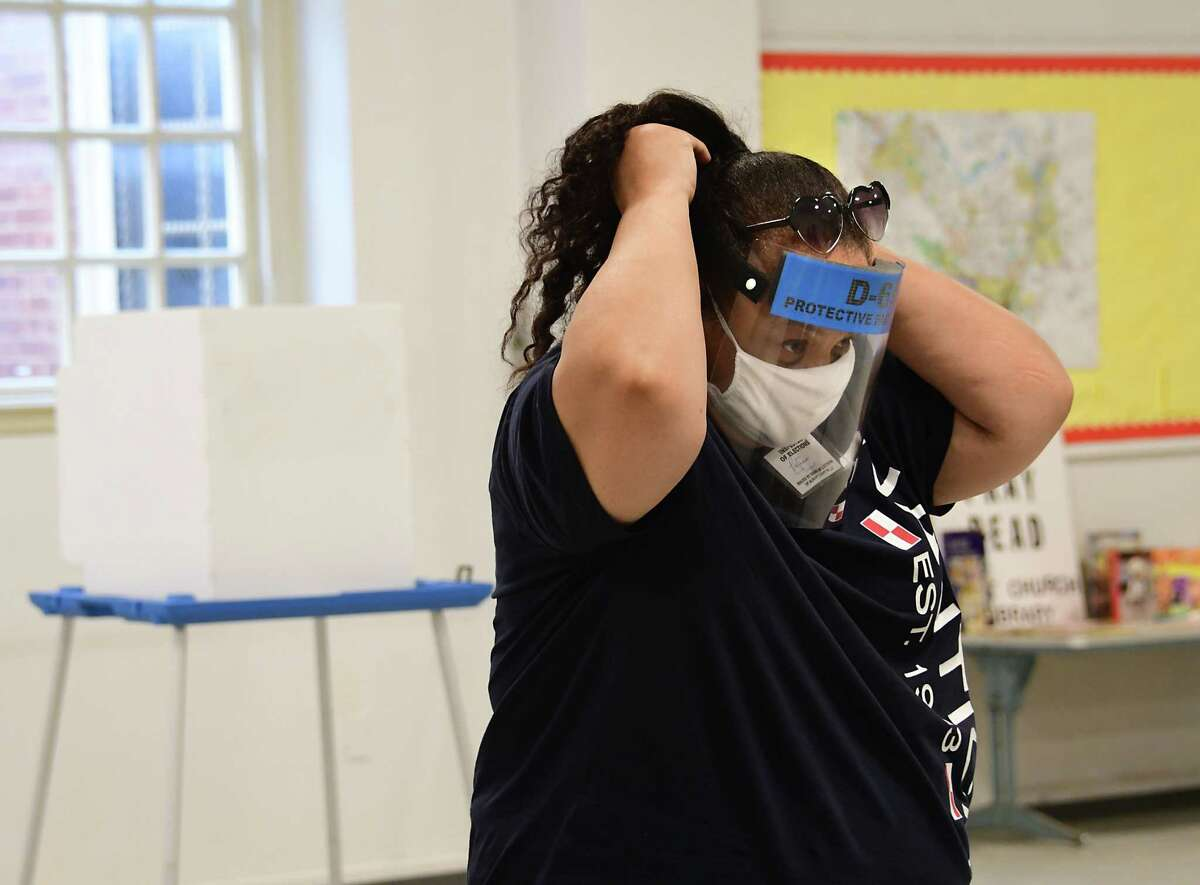 Inspector of Elections worker Patricia Thompson puts on her face shield during primary day at The First Church on Tuesday, June 23, 2020 in Albany, N.Y. (Lori Van Buren/Times Union)