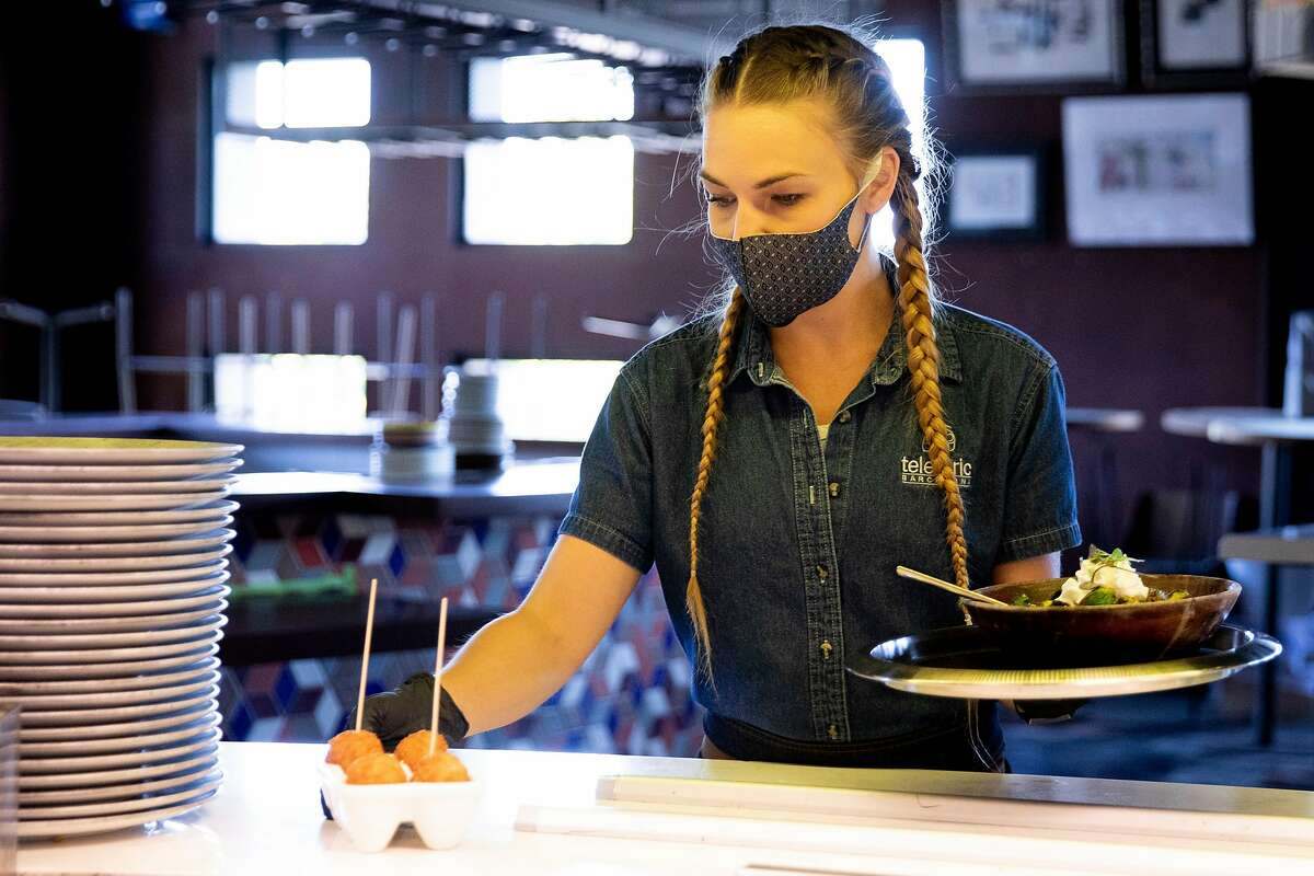 Evelyn Bruce sports a mask and gloves while serving food to customers at Teleferic Barcelona in Walnut Creek, Calif. Tuesday, June 9, 2020. They Bay Area is opening at a fairly fast pace, with Contra Costa County announcing plans this week to reopen indoor dining and hair salons soon, while it reports near-record new cases.