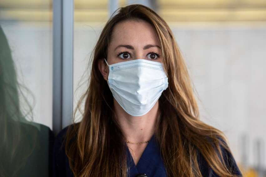 Nurse Practitioner Brooke Carpenter wears a mask while posing for a portrait outside of the California Pacific Medical Center Van Ness Campus Emergency Room in San Francisco, Calif. Friday, June 5, 2020. Carpenter took an unpaid leave of absence during the pandemic surge to travel to New York and volunteer at a hospital working in a makeshift ICU leading a team treating COVID-19.