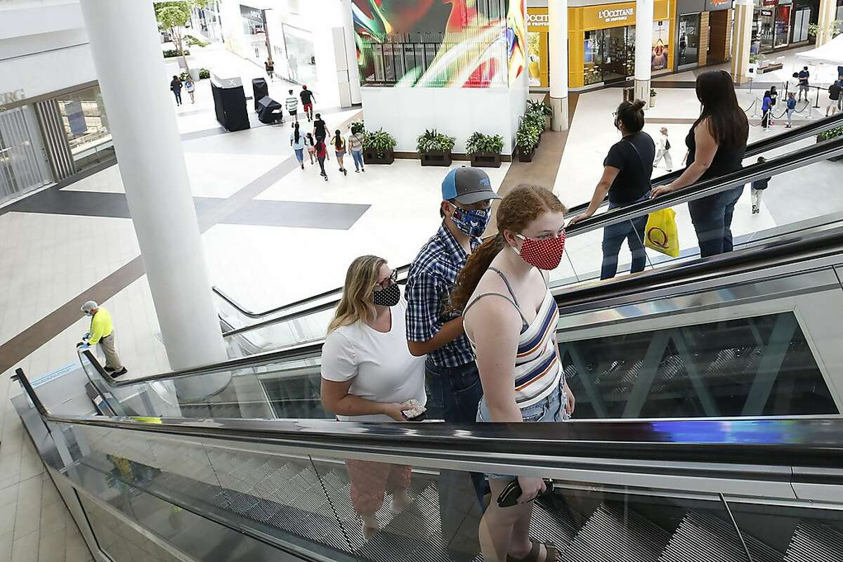 People wearing masks take an escalator to the second floor of the Arden Fair Mall in Sacramento on May 29, 2020.