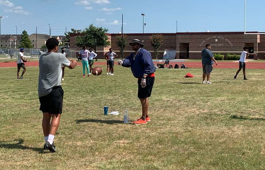 Alief Taylor coach Shawn Gray flips a ball to a quarterback during a passing drill June 17 at Taylor High School. Gray begins his first year as Lions head coach after 13 years as offensive coordinator at Bush. Photo: Jack Marrion