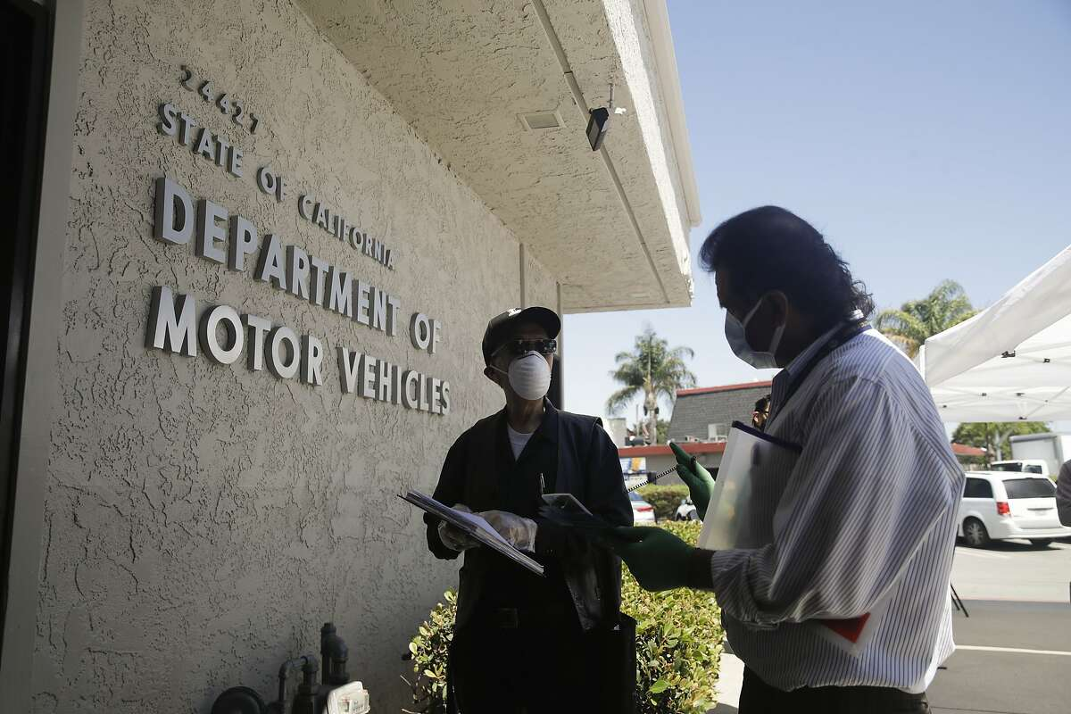 A customer is assisted at a Department of Motor Vehicles office, Thursday, May 28, 2020, in Newhall, Calif.