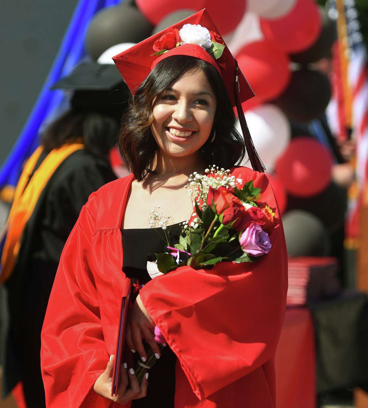 Central High School graduate Wendy Benitez walks with her diploma during day two of the school's three day drive up graduation ceremony at the school in Bridgeport, Conn. on Tuesday, June 23, 2020.