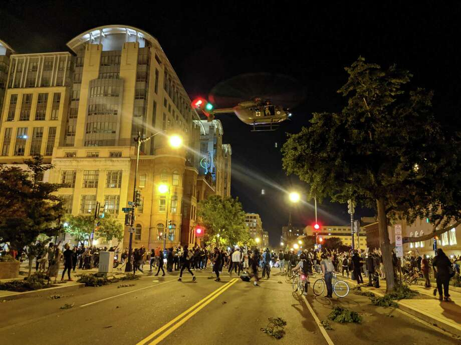 A Lakota helicopter from the D.C. Army National Guard hovers over an intersection in downtown Washington on June 1. Photo: Photo Courtesy Of Sam Ward / Photo by Sam Ward