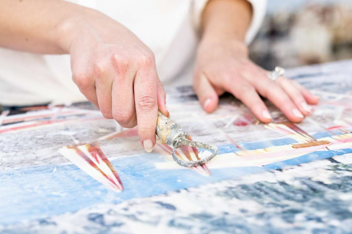 Kayla Barker in working with her photo encaustic work in her studio.