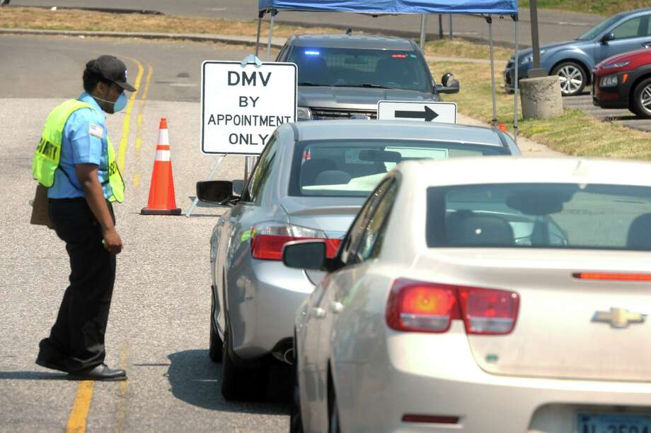 A security guard checks motorists in as they arrive for appointments at the state DMV office in Bridgeport, Conn. June 23, 2020. Photo: Ned Gerard / Hearst Connecticut Media / Connecticut Post