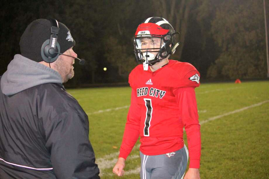 Reed City football coach Monty Price (left) talks with his son and quarterback Jackson Price during the 2018 season. (Pioneer file photo)