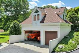 """A guest suite, with a bedroom and full bath, has been incorporated into the design of one of the garages at 21 Harkim Road, Greenwich. This unique 1.5-acre property comprises a four-bedroom transitional main house with both attached and detached garaging for up to 18 cars - """"a car collector's dream,"""" according to its Houlihan Lawrence listing agent, Julie Church."""