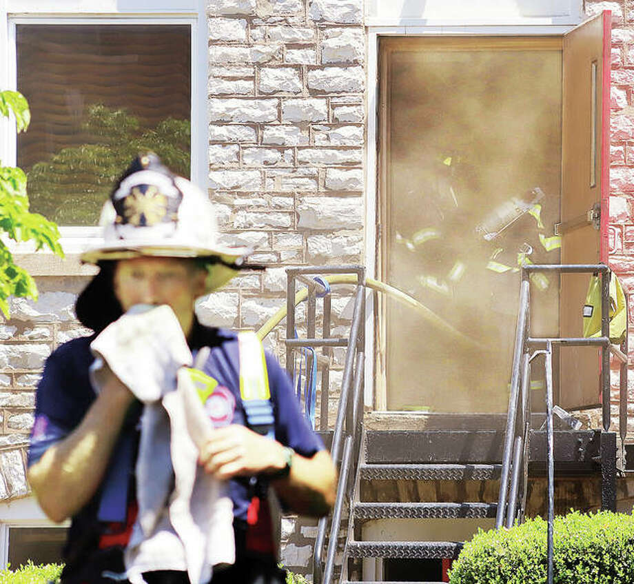 A firefighter wipes away sweat Tuesday as others in the background work to get smoke under control inside the building connected to the sanctuary at St. Paul's Episcopal Church at 3rd and Market streets in Alton. A fire in the basement of the building triggered a massive response from Alton, Godfrey, East Alton and Black Jack, Missouri with fire departments on the scene all day. The Illinois State Fire Marshal's Office is assisting with the investigation. No injuries were reported.