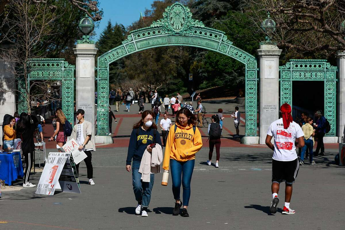 (L-r) Chris Shi, 21 wears a mask while chatting with Monica G. on the UC Berkeley campus on Wednesday, March 4, 2020 in Berkeley, California. A Berkeley resident recently tested positive to the coronavirus.