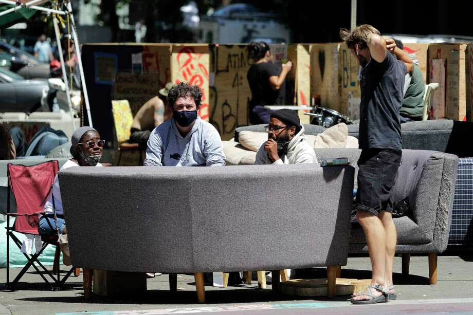 Protesters sit on couches in the street as they visit  where streets are blocked off in what has been named the Capitol Hill Occupied Protest zone, Tuesday, June 23, 2020, in Seattle. Faced with growing pressure to crack down on the area following two weekend shootings, Seattle's mayor said Monday that officials will move to wind down the blocks-long span of city streets taken over two weeks ago. Photo: Elaine Thompson, AP / Copyright 2020 The Associated Press. All rights reserved