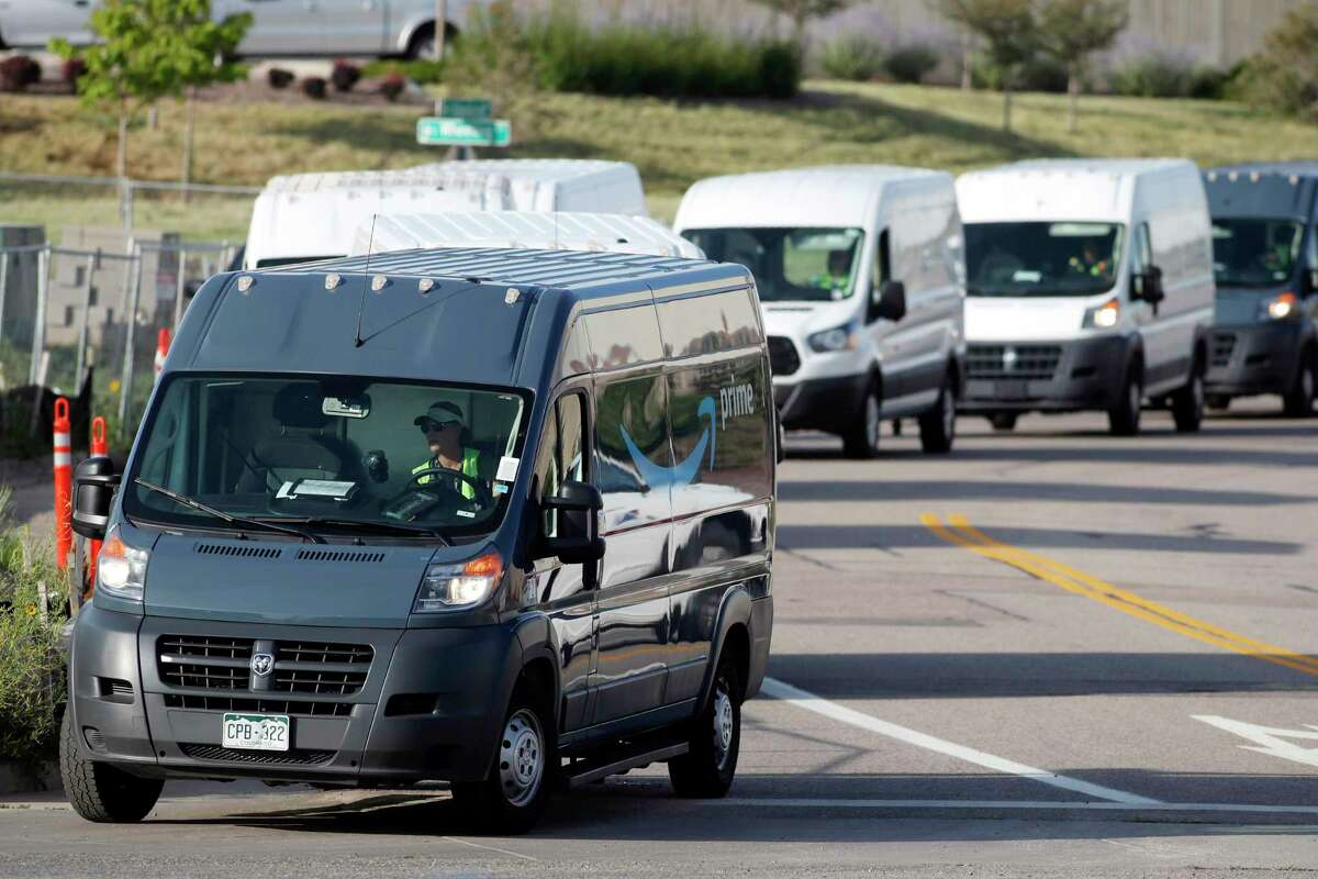 FILE - In this July 30, 2019, file photo, vans queue up to leave an Amazon delivery center in suburban Englewood, Colo. Amazon said Tuesday, June 23, 2020, that its carbon footprint rose 15% last year, even as it launched initiatives to reduce its harm on the environment. (AP Photo/David Zalubowski, File)