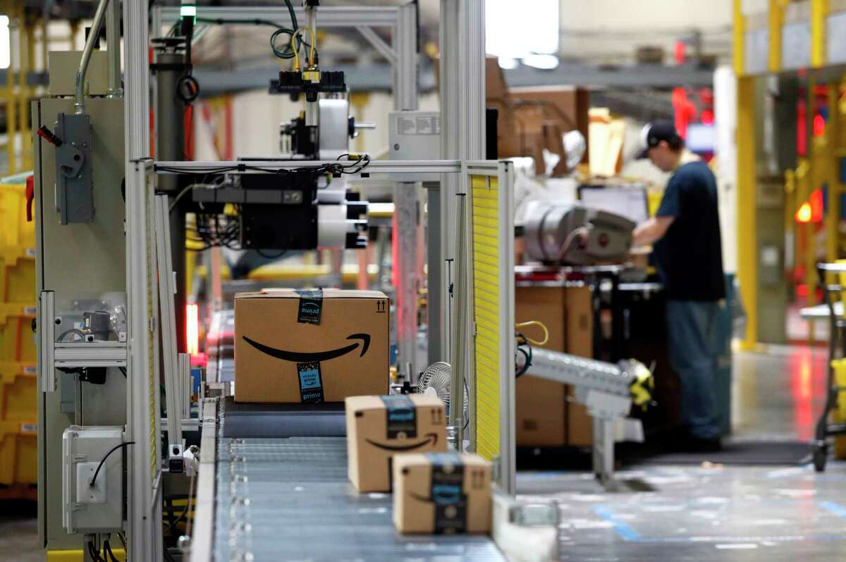 FILE - In this Aug. 3, 2017, file photo, packages pass through a scanner at an Amazon fulfillment center in Baltimore. Amazon said Tuesday, June 23, 2020, that its carbon footprint rose 15% last year, even as it launched initiatives to reduce its harm on the environment. (AP Photo/Patrick Semansky, File)