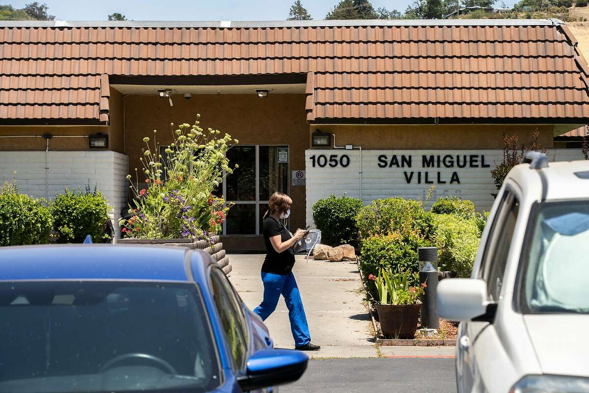 A person walks outside the San Miguel Villa nursing home on Tuesday, June 23, 2020, in Concord, Calif.