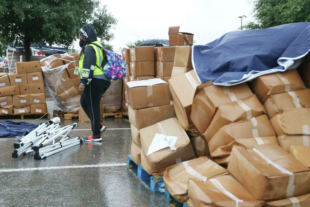 A stack of boxes packed with food waits to be checked out in the parking lot of Toyota Field after a thunderstorm swept through the area, delaying a San Antonio Food Bank mega distribution event. High winds and rain caused damage, but volunteers and staff quickly cleaned up and got the line moving after the storm passed.