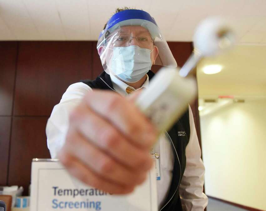 File photo showing receptionist Rick Auz demonstrating the temperature screening required for all patients at Greenwich Hospital in Greenwich, Conn., taken on Tuesday, June 23, 2020. However, Buller and Urban disagree on lowering the BMI threshold for obesity from 40 to 30. Buller said it is