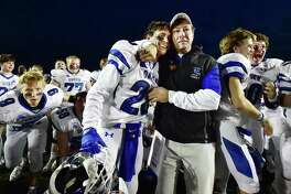 Darien head coach Rob Trifone embraces his son, Robert (28) following the Wave's 39-7 victory over the Shelton Gaels in the 2015 Class LL state football final in New Britain.