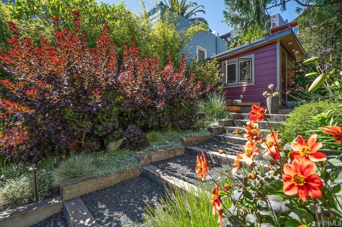 The rear of the lot features planter boxes and a home office. The
