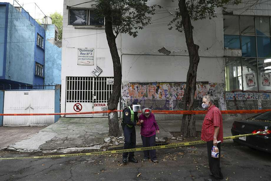 A police officer helps an elderly woman to a safer place after an earthquake in Mexico City, Tuesday, June 23, 2020. The earthquake struck near the Huatulco resort in southern Mexico on Tuesday morning, swayed buildings in Mexico City and sent thousands fleeing into the streets. (AP Photo/Eduardo Verdugo) Photo: Eduardo Verdugo, Associated Press