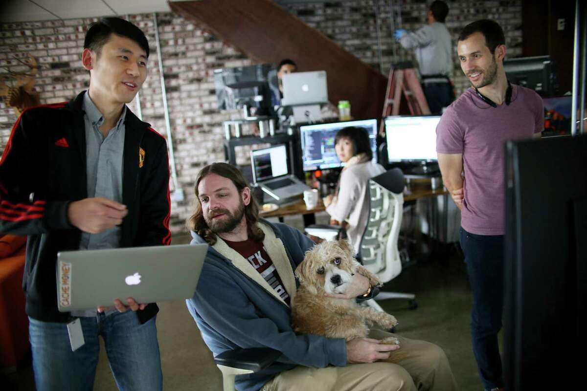 Kan Wang, left, an engineer at Zeeto and an H-1B Visa holder, looks over a project with teammates. The Trump administration has put a hold on many categories of foreign workers and curbed immigration visas through the end of the year.