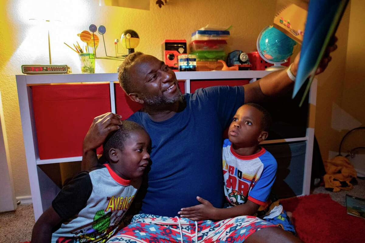 """George Williams, who is on the board of the Carver Community Cultural Center, reads """"The Rhino Who Swallowed a Storm"""" to his children, Aaron, 7, left, and Jaxon, 6, at bedtime. Williams is bringing his bedtime story ritual to a wider audience through """"Storytime with Dr. Williams,"""" a new online series produced by the Carver."""