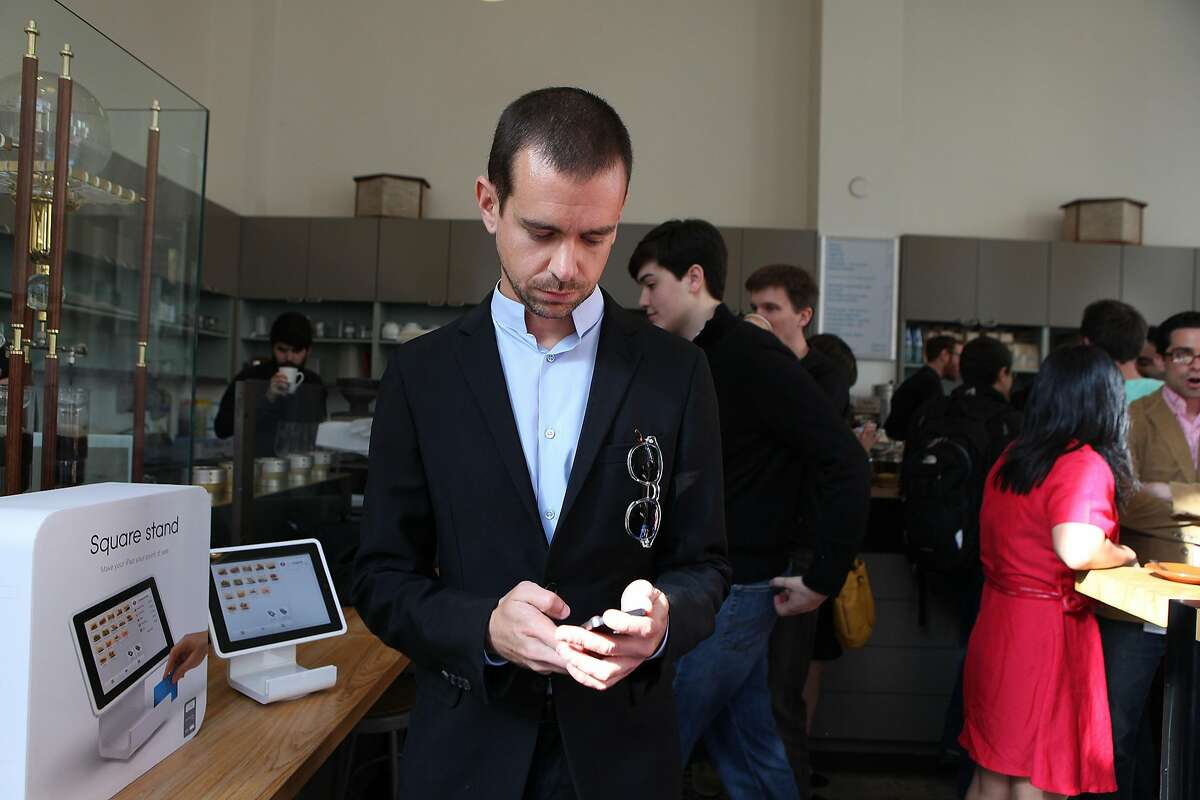 Square CEO Jack Dorsey (front) introduces the Square Stand (left), a new point of sale device, at Blue Bottle in San Francisco, Calif., on Tuesday, May 14, 2013. The Stand hardware secures an iPad with an integrated credit card reader and has plug ins for barcode scanners, customer receipts, and other merchant needs.