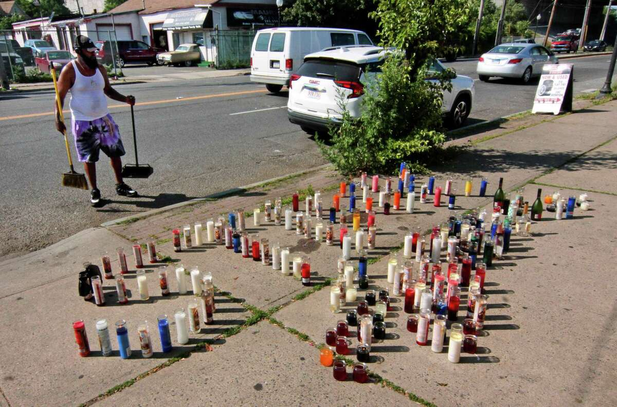 A resident cleans up the sidewalk and street where a memorial has been set up for an apparent homicide victim on Fairfield Avenue near Albion Street in Bridgeport on Tuesday. The memorial was set up for an 18-year old male who was found slumped in the driver's seat with an apparent gunshot wound to the head.