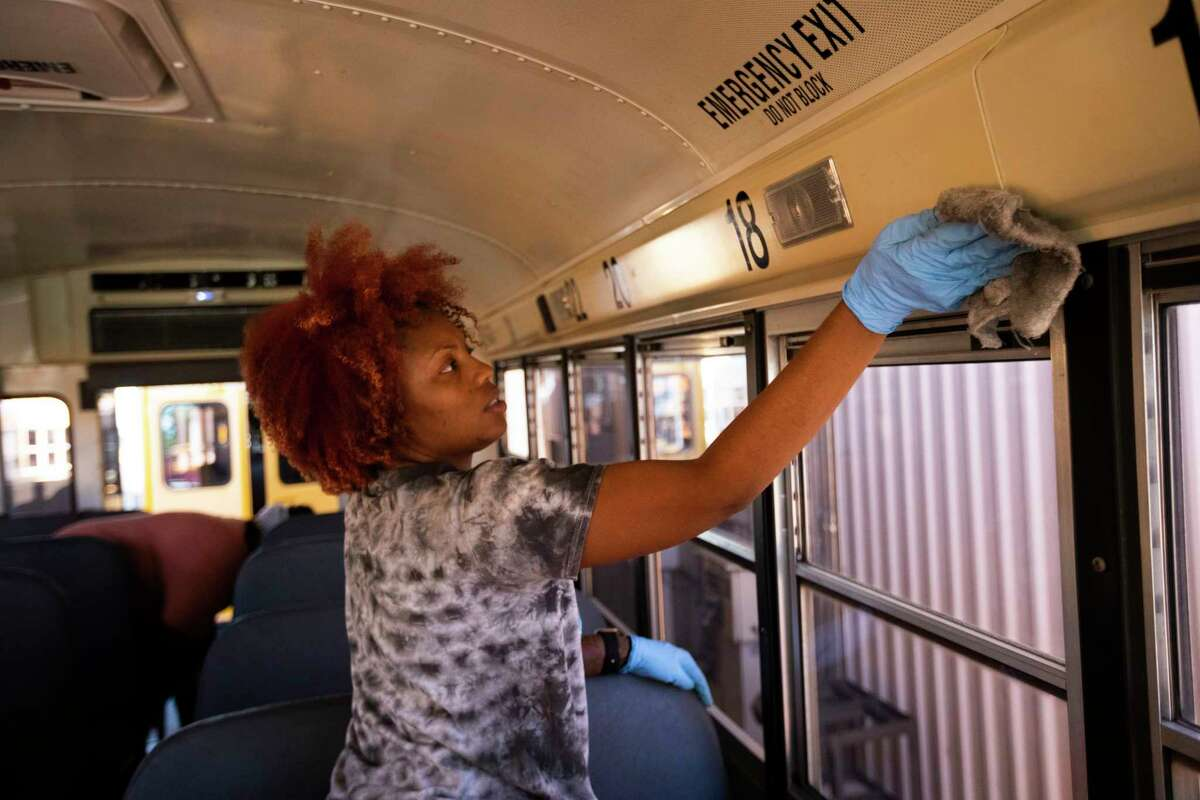 Humble ISD bus driver Regina Bell disinfects the windows of a Humble ISD school bus on Thursday, June 11, 2020, in Humble.