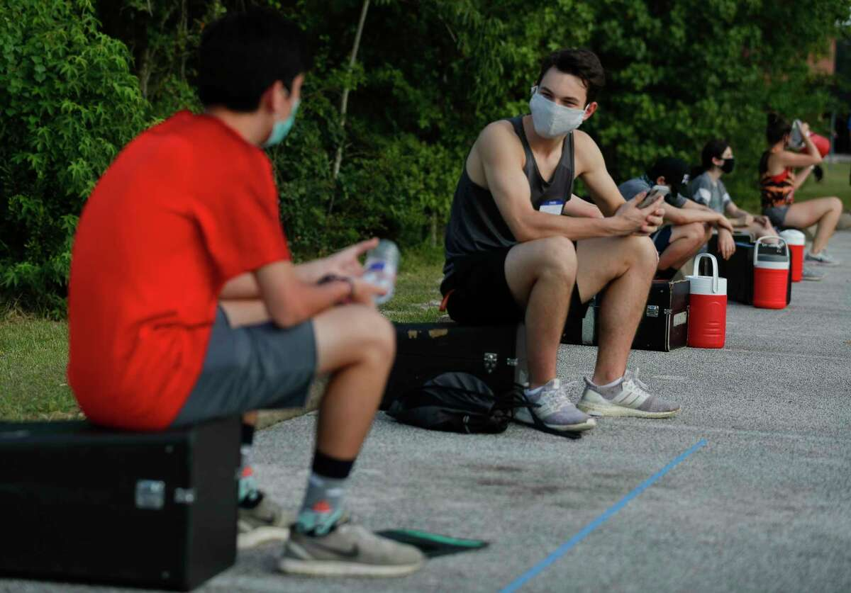 Joseph Templet, right, talks with Sebastian Penedo six feet apart as they wait for the start of marching band practice at The Woodlands High School, Wednesday, June 17, 2020, in The Woodlands. Students were able to participate under social distancing guidelines and with regular disinfecting of equipment, according to regulations set by the University Interscholastic League.
