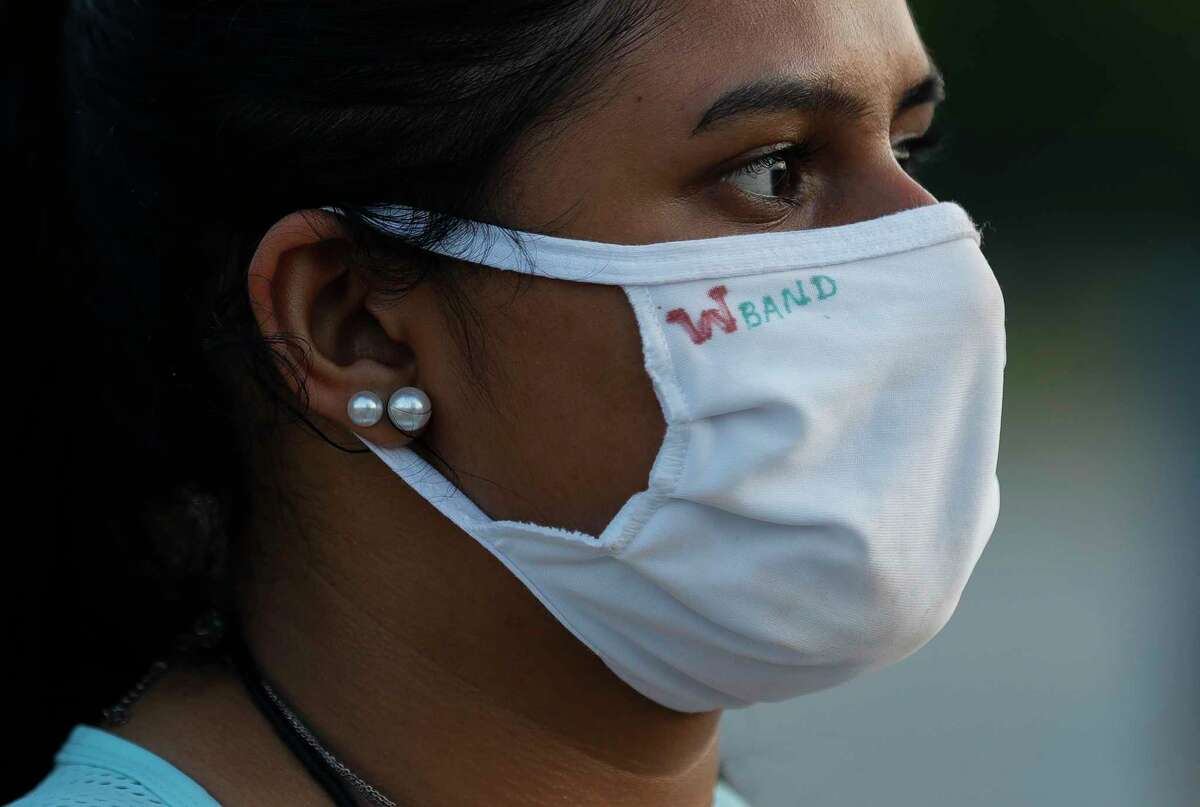 Mahika Peri wears a face mask during marching band practice at The Woodlands High School, Wednesday, June 17, 2020, in The Woodlands. Students were able to participate under social distancing guidelines and with regular disinfecting of equipment, according to regulations set by the University Interscholastic League.