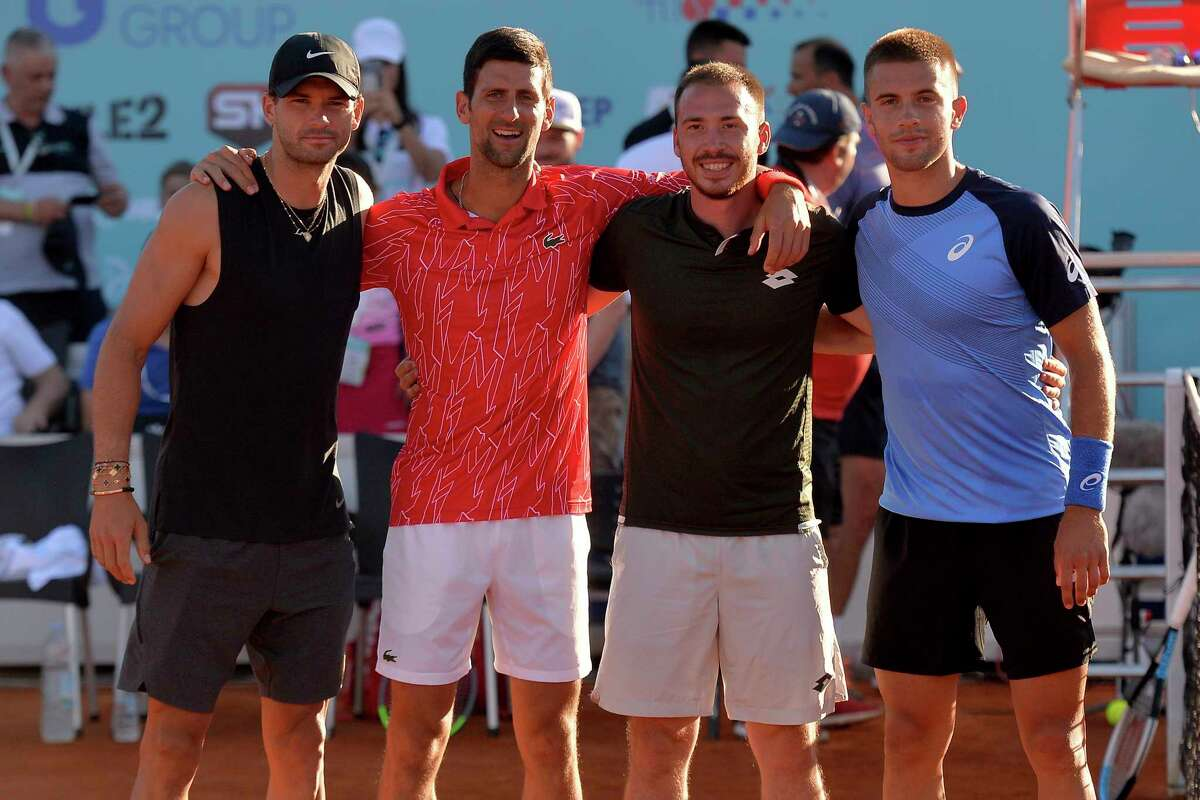 In this photo taken June 19, 2020, Serbian tennis player Novak Djokovic, second left, poses with Bulgaria's Grigor Dimitrov, left, Serbia's Viktor Troicki and Croatia's Borna Coric, right, at a tournament in Zadar, Croatia. Novak Djokovic has tested positive for the coronavirus after taking part in a tennis exhibition series he organized in Serbia and Croatia. (AP Photo/Zvonko Kucelin)