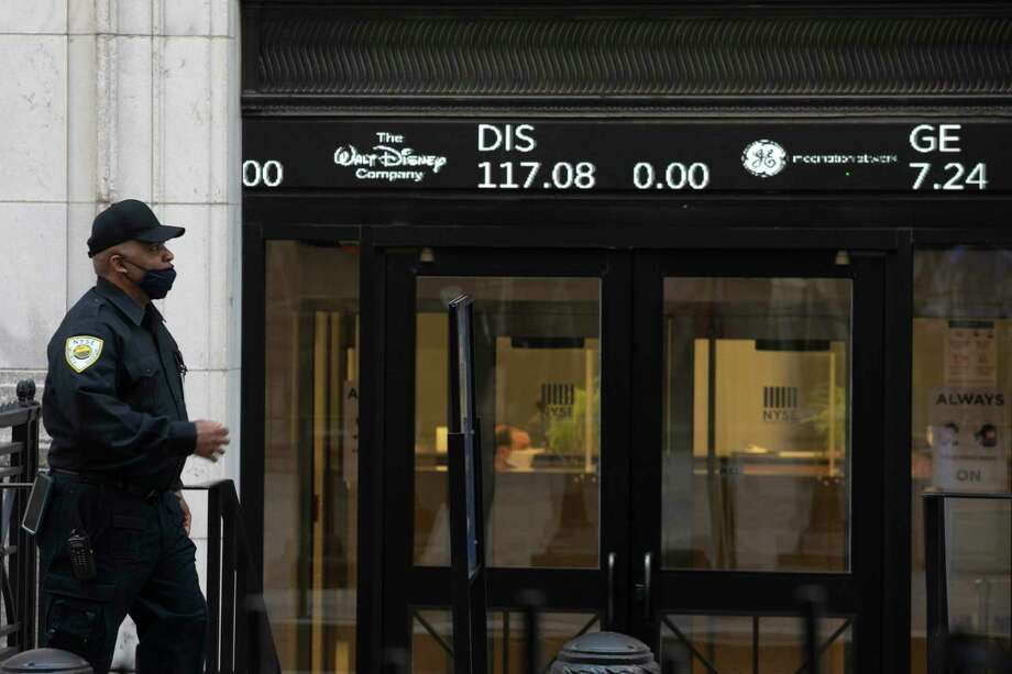 A security guard walks by a stock ticker on the front door of the New York Stock Exchange, Tuesday, June 16, 2020. Stocks are rising sharply in early trading on Wall Street after retail sales in the U.S. soared by a record 17.7% from April to May, double what economists were expecting and a welcome sign that spending is partially rebounding after the devastating coronavirus shutdowns. (AP Photo/Mark Lennihan) Photo: Mark Lennihan, STF / Associated Press / Copyright 2020 The Associated Press. All rights reserved