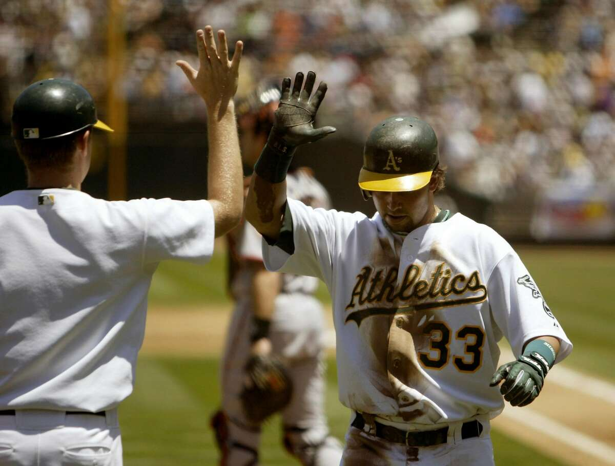 Athletics's Nick Swisher, gets a high five from the batboy after scoring in the bottom of the second inning of play on a Jason Kendall double. The Oakland Athletics played the San Francisco Giants at McAfee Coliseum in Oakland, Ca., on Sunday, June 26, 2005.