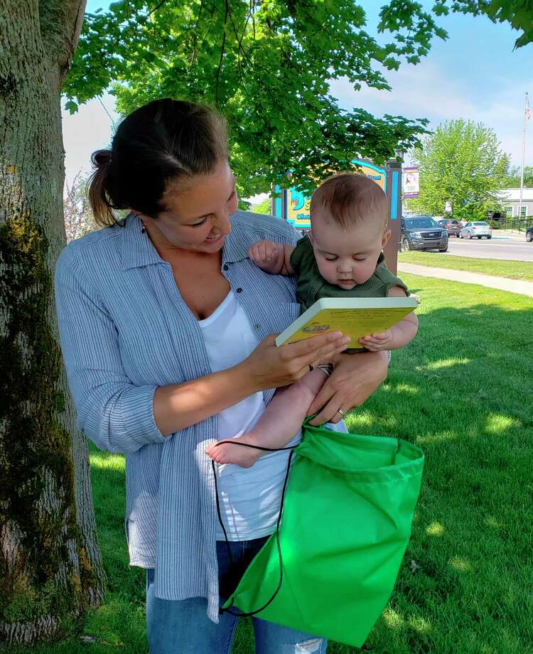 Brenna Nugent shows a new book to her daughter Josie. (Submitted photo)