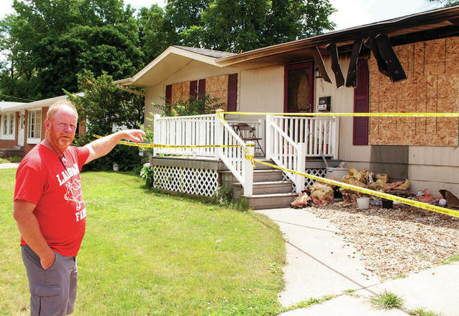 Troy Zoellner points to one of the windows he and his son helped board up after a fire at a Hall Drive home that claimed two lives. Photo: Darren Iozia | Journal-Courier