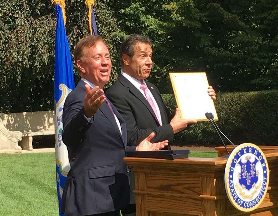 Connecticut Gov. Ned Lamont, left, and New York Gov. Andrew Cuomo share a laugh after Lamont gave Cuomo a mounted Connecticut fishing license at the governor's mansion in Hartford, Sept. 25, 2019. Photo: Dan Haar/Hearst Connecticut Media