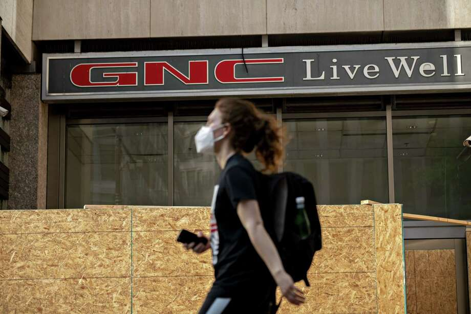 A pedestrian wearing a protective mask walks past a boarded up GNC store in Washington, D.C. on June 4, 2020. Photo: Bloomberg Photo By Andrew Harrer. / © 2020 Bloomberg Finance LP