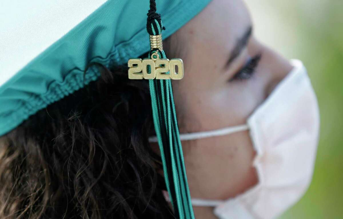 """Valedictorian Sierra Morgado's graduation tassel has """"2020"""" on it as she listens during a graduation ceremony for the senior class of Chambers High School at Homestead-Miami Speedway, Tuesday, June 23, 2020, in Homestead, Fla. Forty-one seniors graduated from the school and crossed the start-finish line to receive their diplomas, during the coronavirus pandemic."""