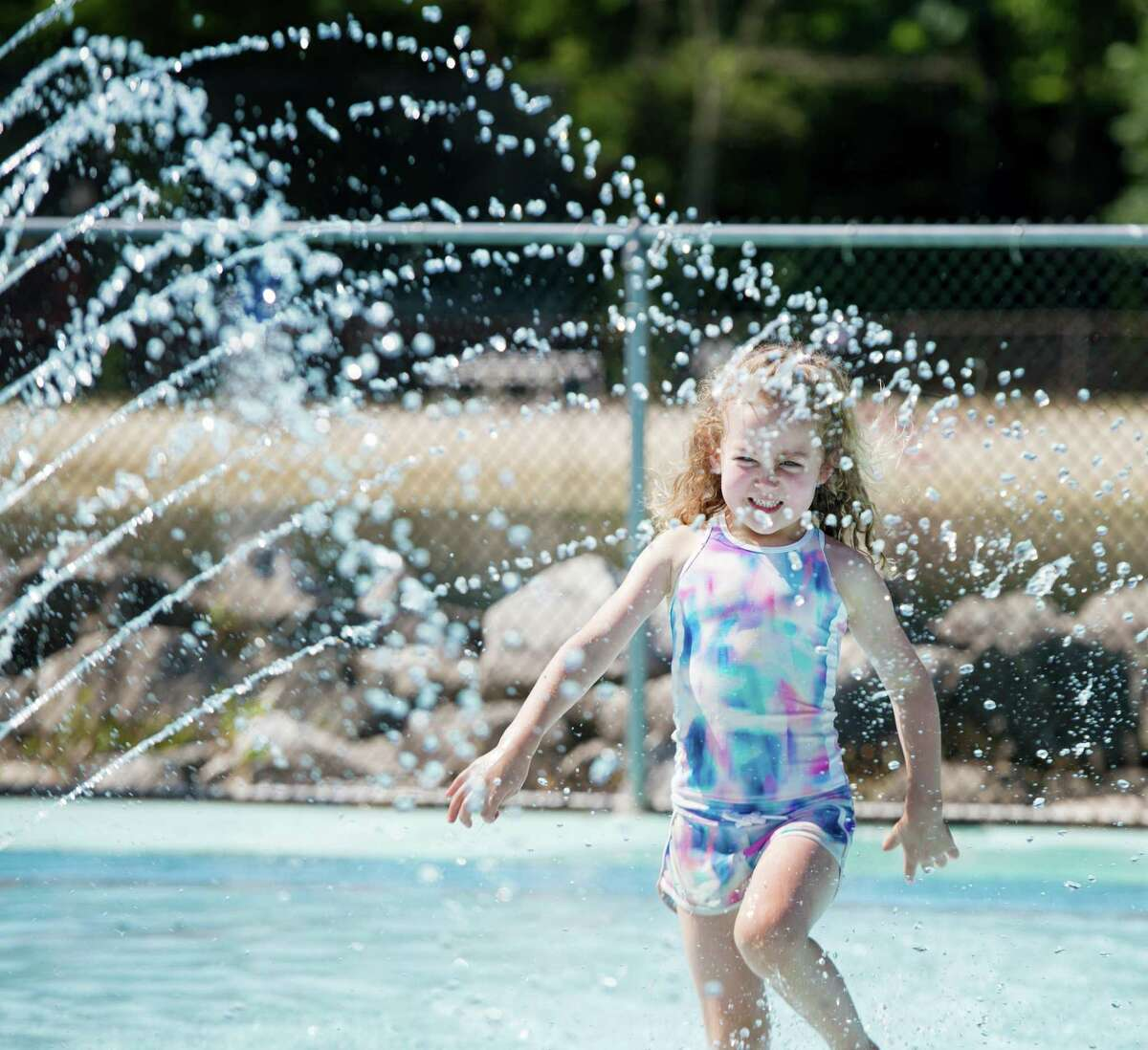 Cecilia McNeil cools off in the splash pad at the Wilton Y's Camp Gordyland on Monday, June 22.