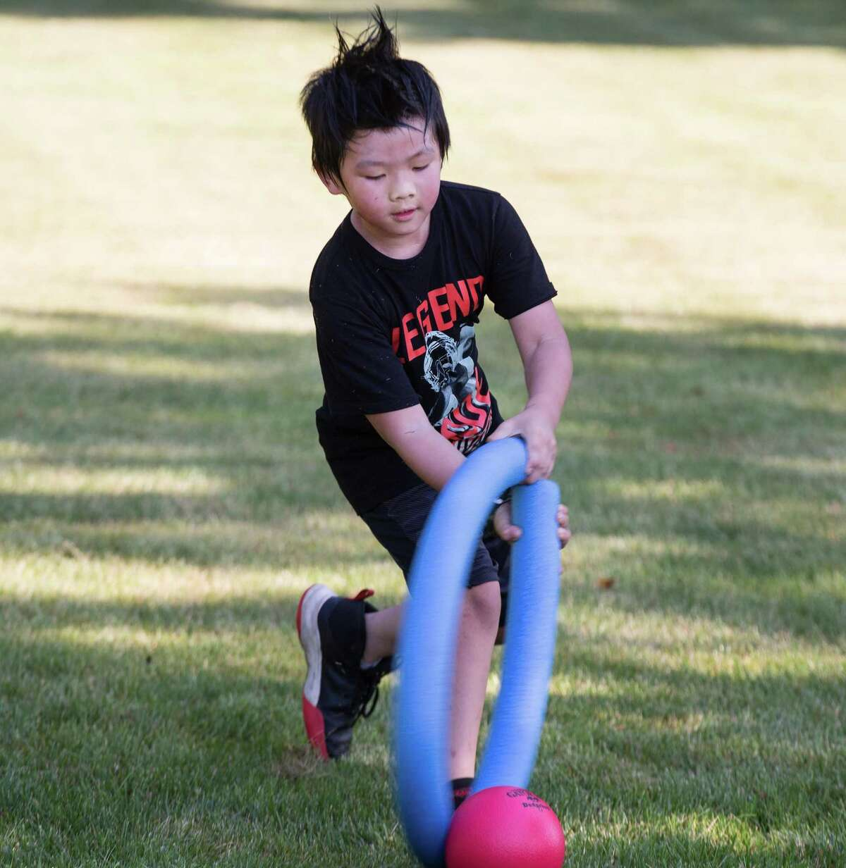 Max Lee hits a ball during a game of noodle hockey on opening day of Camp Looper and Cool Tots.
