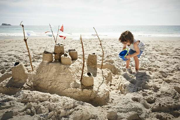 Little boy building sandcastle on beach - stock photo
