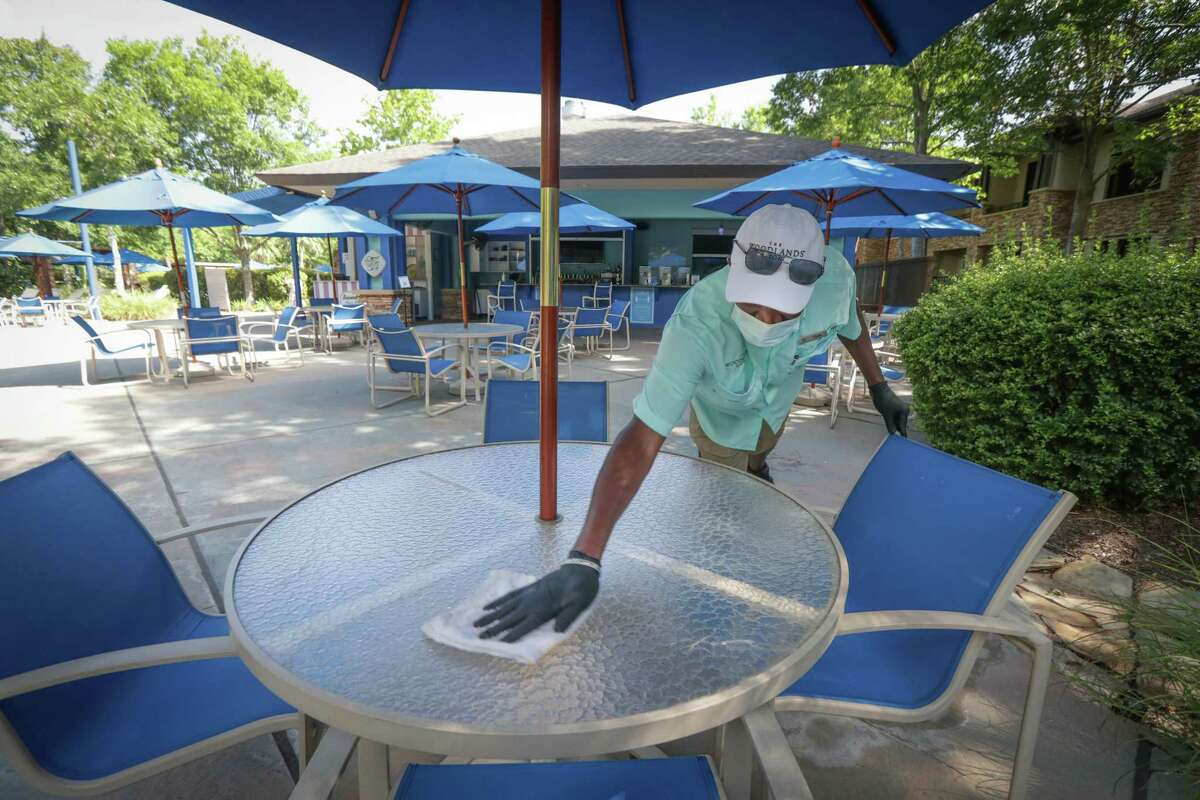 Restaurant server Clyde Tugwell sanitizes a table at The Cool Water Cafe near the Lazy River in The Woodlands Resort Thursday, June 18, 2020, in The Woodlands.