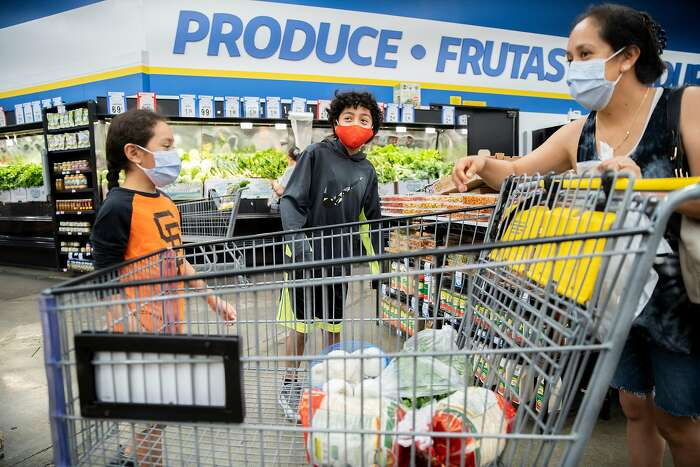 From left: Jacob Barajas, 8, with his brother Abram Barajas, 11, and mother Paulina Barajas shop at FoodMaxx on Thursday, June 11, 2020, in Concord, Calif. The family have switched stores from big-brand supermarkets to discount supermarkets to save money.
