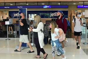 A family traveling to Orlando walk to their gate after getting their boarding tickets at Albany International Airport on Wednesday, June 24, 2020 in Colonie, N.Y. Governor Andrew Cuomo has directed that all travelers arriving in New York State from states heavily impacted by the spread of the Coronavirus are subject to a 14-day quarantine. (Lori Van Buren/Times Union)