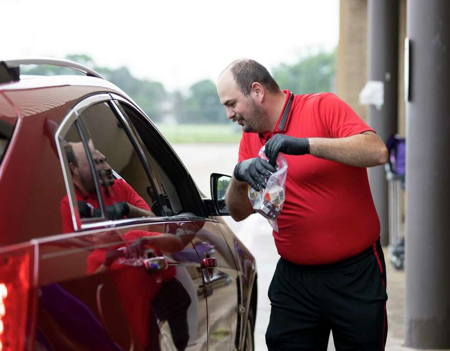 Thomas Kelley, custodian at Hardy Elementary in Willis, distributes bagged breakfast to students in their vehicles, Tuesday, March 23, 2020. Willis ISD started distribution of Child Nutrition Meals which includes bagged breakfast and lunch in response to school closures throughout the county. Photo: Gustavo Huerta, Houston Chronicle / Staff Photographer / Houston Chronicle © 2020