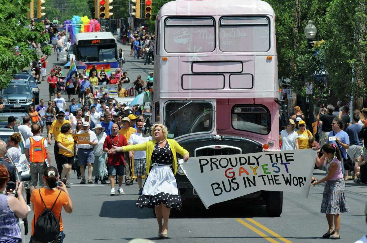 Miss Sherry Pie, left, and Laura Ferreri, hold a banner as they lead the bus for Bettie's Cakes as they make their way down Lark Street during the 2012 Capital Pride Parade, on Sunday June 10, 2012 in Albany, NY. The bus was later named best vehicle in the parade. (Philip Kamrass / Times Union)