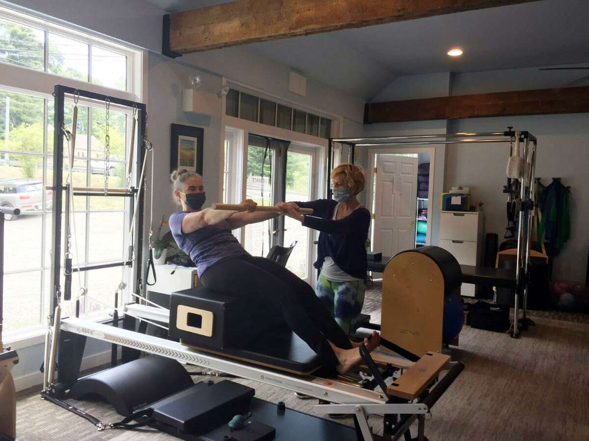 Owner Mary Beth Young, right, works with Cristin Wallace at The Pilates Advantage in Wilton. Young is cautiously optimistic that her business will survive after being closed for four months during the coronavirus pandemic.